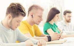 Barn och smarta studenter som lär i ett klassrum Fotografering för Bildbyråer