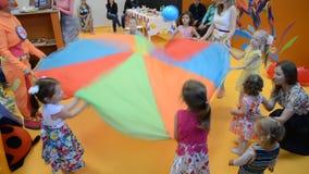 Barn och tecknaren spelar med en boll En ferie i klubba för barn` s arkivfilmer