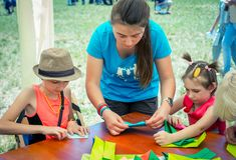 Barn och ung flicka - volontär på origamiseminariet royaltyfri fotografi