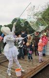 Barn och vuxen människaklocka i beundran på såpbubblatillverkaren Royaltyfri Foto