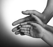Barn och vuxen människahänder Arkivbilder