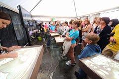 Barn och vuxna människor på mästarklass av sandanimeringen Royaltyfria Foton