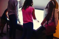 Barn och vuxna människor som använder den växelverkande pekskärmen i ett museum Modernt teknologibegrepp Selektivt fokusera Arkivfoton