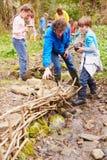 Barn och vuxna människor som ut bär beskyddarbete på ström Arkivbild