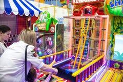 Barn och vuxna människor spelar på enarmade banditerna, dragningar i köpcentret Familjer med barn har gyckel- och lekgallerit arkivfoto