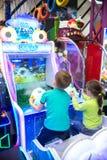 Barn och vuxna människor spelar på enarmade banditerna, dragningar i köpcentret Familjer med barn har gyckel- och lekgallerit royaltyfri foto