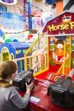 Barn och vuxna människor spelar på enarmade banditerna, dragningar i köpcentret Familjer med barn har gyckel- och lekgallerit royaltyfria foton