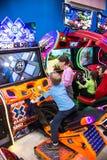 Barn och vuxna människor spelar på enarmade banditerna, dragningar i köpcentret Familjer med barn har gyckel- och lekgallerit fotografering för bildbyråer