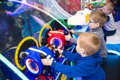 Barn och vuxna människor spelar på enarmade banditerna, dragningar i köpcentret Familjer med barn har gyckel- och lekgallerit arkivbilder