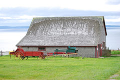 Barn and old farm wagon. Exterior of barn by sea with old farm wagon in green foreground field Royalty Free Stock Image