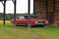 Barn. Old forgotten car sitting under the roof of an old barn rusting away Royalty Free Stock Image