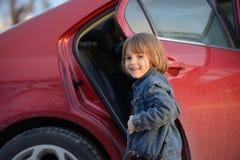 Barn omkring som ska fås in i bilen Arkivbild