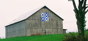 A barn with an ornamental & x22;quilt& x22; in a green horse field Stock Images