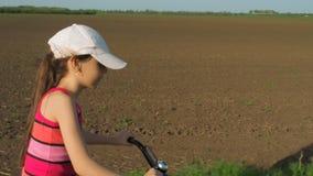 Barn på en cykel Liten flicka på en cykel i bygden Flickan rider en cykel på en landsväg lager videofilmer