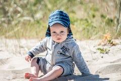Barn på en strand som sitter på sand royaltyfria foton