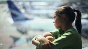 Barn på flygplatsen nära fönstret som ser flygplan och väntar på tid av flyget lager videofilmer