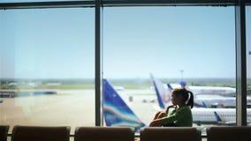 Barn på flygplatsen nära fönstret som ser flygplan och väntar på tid av flyget arkivfilmer