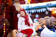 Barn på ganska jul Unge som rider Xmas-karusell royaltyfri foto