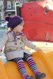 Barn på glidbana i lekplats. Utomhus- parkera. royaltyfri foto