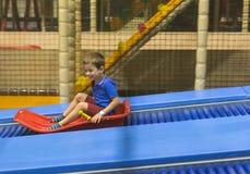 Barn på glidbanaritt i lekområde Royaltyfri Fotografi