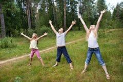Barn på gräsmatta av skogen och tycker om liv i sportar Arkivbilder