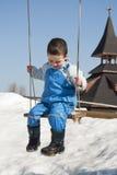 Barn på gunga på vintern Arkivbild
