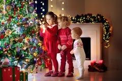 Barn på julgranen Ungar på spisen på Xmas-helgdagsafton royaltyfri foto