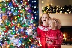 Barn på julgranen Ungar på spisen på Xmas-helgdagsafton royaltyfri fotografi