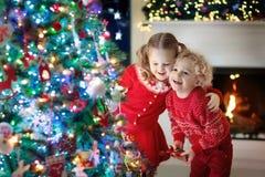 Barn på julgranen Ungar på spisen på Xmas-helgdagsafton royaltyfria bilder