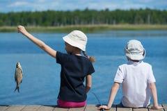 Barn på skeppsdockan med fisken Royaltyfri Bild