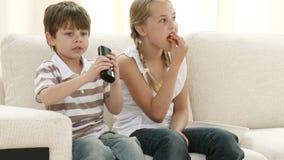 Barn på soffan som äter, och hållande ögonen på television stock video
