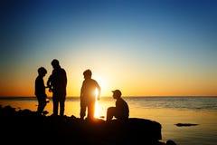 Barn på stranden som fiskar Solnedgångskott, bakre sikt sun för hav för bakgrundsfiordsstråle royaltyfri foto