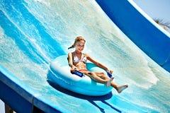Barn på vattenglidbana på aquapark. Royaltyfri Bild