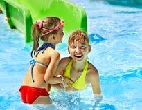 Barn på vattenglidbana på aquapark. Arkivbilder