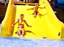 Barn på vattenglidbana på aquapark. Arkivbild