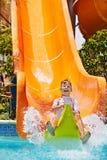 Barn på vattenglidbana på aquapark. Royaltyfria Bilder