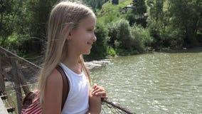 Barn p? bron i berg, unge som fotvandrar i natur, flicka som ser en flod, str?m lager videofilmer