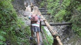 Barn p? bron i berg, unge som fotvandrar i natur, flicka som ser en flod, str?m arkivfilmer