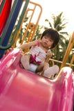Barn på en glidbana i lekplats Arkivbild