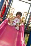 Barn på en glidbana i lekplats Royaltyfria Bilder