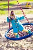 Barn på lekplatsgunga Royaltyfria Bilder