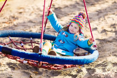 Barn på lekplatsgunga Royaltyfri Foto