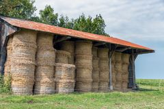 Barn with pile of haystacks in Normandy, France. Rural landscape and open barn with pile of haystacks in Normandy, France stock image