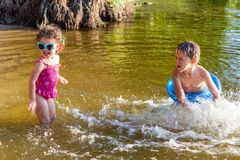 Barn plaskar vatten på stranden Royaltyfri Fotografi