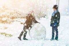 Barn pojke och flicka i snöig vinter gör utomhus en stor snögubbe royaltyfri foto