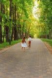 Barn pojke och flickakörning längs banan i parkera royaltyfri fotografi