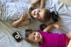 Barn pojke och flickasyskongrupp som spelar med kameror f Arkivfoton