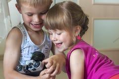 Barn pojke och flickasyskongrupp som spelar med kameror f royaltyfria bilder