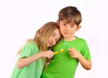 Vård- - pojken och flickan borstar deras tänder Royaltyfri Foto