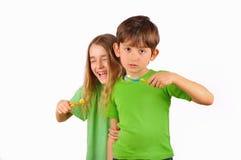 Barn, pojken och flickan borstar deras tänder och skrattar Arkivfoton